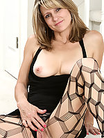 Blonde MILF Veronica B shows her pussy through fishnet stockings